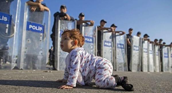Migranti, baby profuga gattona verso la polizia. Il tenero e drammatico scatto diventa virale