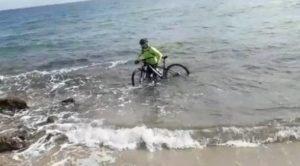 Coronavirus, ciclista entra in mare con la sua bici per cercare di evitare un controllo